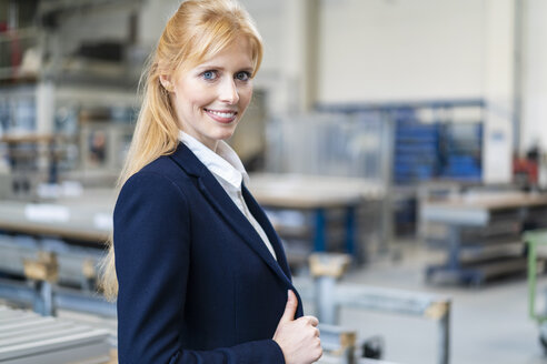 Portrait of smiling businesswoman in factory - DIGF06155