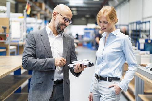 Businessman and businesswoman examining workpiece in factory - DIGF06173
