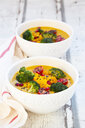 Curry dish with pumpkin, sweet potato, brokkoli, tomato, pomegranate seeds and black sesame in bowl - LVF07853