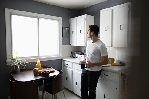Thoughtful young Latinx man drinking coffee in morning kitchen - HEROF28150