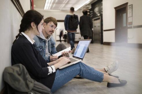 University students using laptop on floor in corridor - HEROF28231