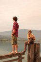 Young couple looking out from pier, Lake Annecy, Annecy, Rhone-Alpes, France - CUF49523
