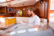 Young man in sailboat cabin reading book - CUF49592