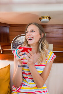 Young woman in sailboat cabin holding cup of coffee - CUF49595