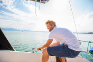 Young man sailing on Chiemsee lake, Bavaria, Germany - CUF49601