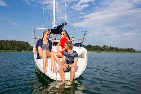 Young man and adult women sitting chatting on sailboat on Chiemsee lake, Bavaria, Germany - CUF49616