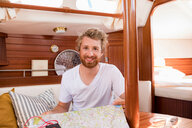 Young man in sailboat cabin with folding map - CUF49625