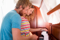 Young couple in sailboat cabin using coffee machine - CUF49628