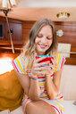 Young woman enjoying coffee in sailboat cabin - CUF49631