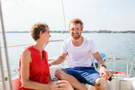 Young man and mature woman laughing on sailboat on Chiemsee lake, Bavaria, Germany - CUF49634
