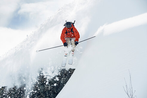 Male skier skiing mid air down snow covered mountain, Alpe-d'Huez, Rhone-Alpes, France - CUF49655