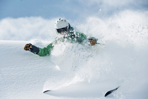 Male skier speeding down snow covered mountain, Alpe-d'Huez, Rhone-Alpes, France - CUF49658
