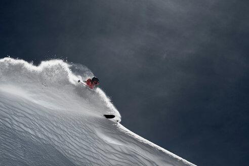 Male skier skiing down steep mountainside, Alpe-d'Huez, Rhone-Alpes, France - CUF49670