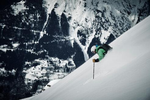 Male skier skiing down steep mountainside, Alpe-d'Huez, Rhone-Alpes, France - CUF49676