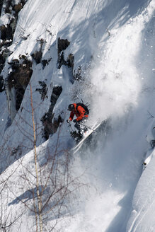 Male skier speeding down rugged vertical mountainside, Alpe-d'Huez, Rhone-Alpes, France - CUF49700