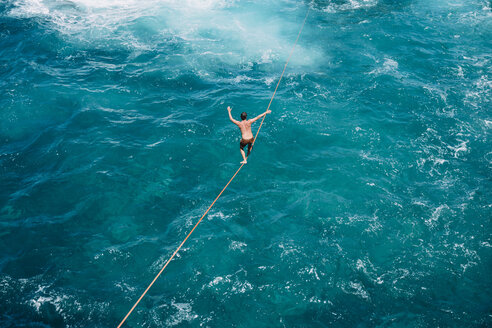 High angle view of carefree young man practicing slacklining over sea - CAVF63027