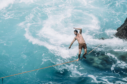 Carefree young man slacklining on rope over sea during sunny day - CAVF63030