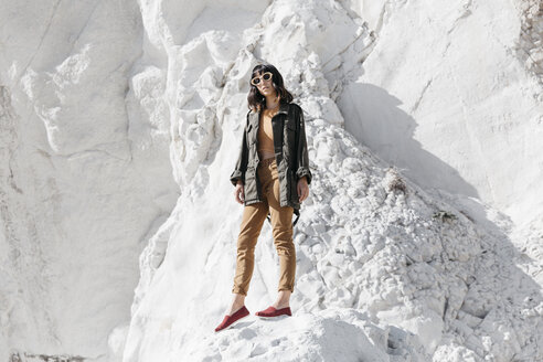 Portrait of woman wearing sunglasses standing on snow covered rock during sunny day - CAVF63048