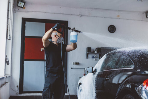 Worker pouring water on car while standing in workshop - CAVF63066