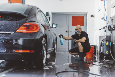 Male worker spraying water on car while crouching in workshop - CAVF63075