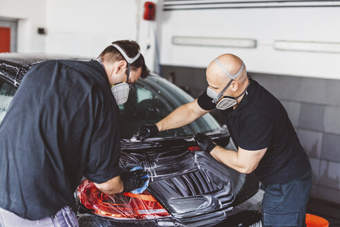 Male workers cleaning car with soap in workshop - CAVF63081
