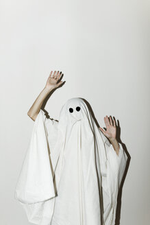 Man in ghost costume gesturing while standing against wall - CAVF63105