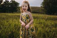 Portrait of happy cute girl standing on grassy field against sky - CAVF63114