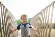 Portrait of cute baby boy playing on outdoor play equipment at playground - CAVF63132