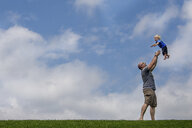 Side view of playful father throwing son in mid-air while standing on grassy field against cloudy sky - CAVF63150