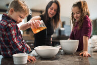 Children watching mother pour honey into bowl - ISF21011