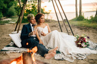 Bride and groom on picnic blanket by lakeside campfire, Lake Ontario, Toronto, Canada - ISF21056