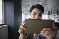 Smiling businessman using digital tablet in office - HEROF28379