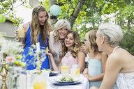 Smiling women family enjoying garden party lunch - HEROF28388