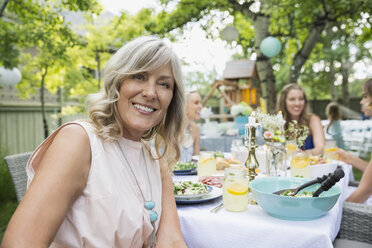 Portrait smiling woman at garden party lunch - HEROF28391