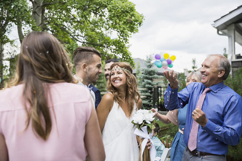 Wedding guests throwing confetti over bride and groom - HEROF28394