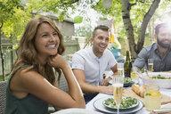 Smiling friends enjoying garden party lunch - HEROF28400