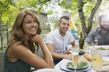 Smiling friends enjoying garden party lunch - HEROF28400