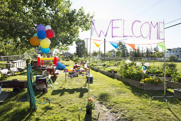 Welcome sign and balloons in sunny community garden - HEROF28415
