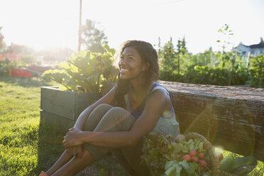 Smiling young woman basket harvested vegetables garden - HEROF28418
