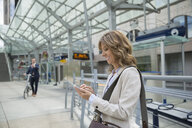 Smiling businesswoman texting on cell phone train station - HEROF28454