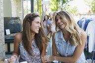 Women laughing at storefront - HEROF28469