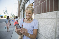 Smiling woman texting with cell phone on sidewalk - HEROF28484