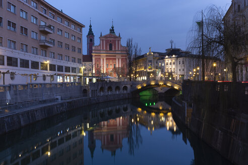Slovenia, Ljubljana, view to city centre with Franciscan Church and lighted Triple Bridge - FCF01731