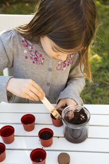Little girl at garden table sowing seeds - LVF07856
