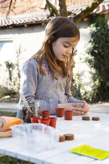 Little girl at garden table sowing seeds - LVF07859