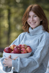 Portrait of redheaded teenage girl holding bowl of apples - LBF02413