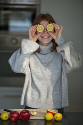 Laughing teenage girl holding lemon halves in front of her eyes - LBF02416