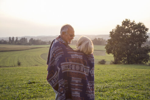 Happy senior couple standing on a meadow at sunset sharing blanket - MAMF00479