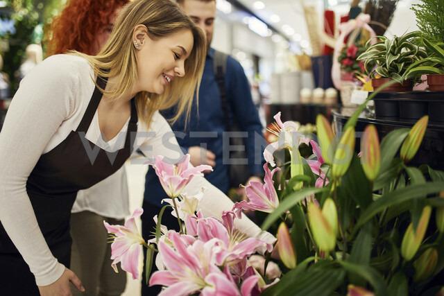 Shop assistant advising couple in flower shop - ZEDF01965