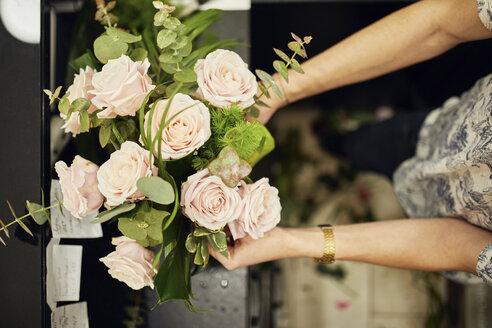 Close-up of florist arranging flowers in flower shop - ZEDF01968
